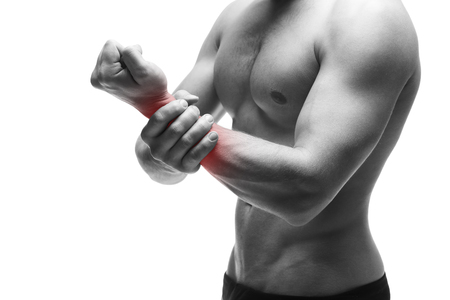 enhanced health: Pain in the hand. Muscular male body. Handsome bodybuilder posing in studio. Isolated on white background with red dot. Black and white photography Stock Photo