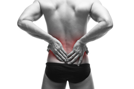pyelonephritis: Man with backache. Muscular male body. Handsome bodybuilder posing in studio. Isolated on white background with red dot. Black and white photography
