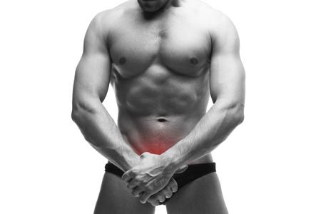 pene: Hombre con dolor en la próstata. Carrocería masculina muscular. Guapo fisicoculturista posando en el estudio. Aislado en el fondo blanco con punto rojo. fotografía en blanco y negro