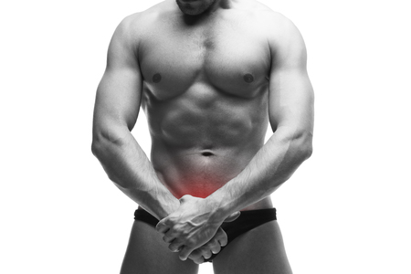 impotence: Man with pain in the prostate. Muscular male body. Handsome bodybuilder posing in studio. Isolated on white background with red dot. Black and white photography
