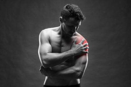 enhanced health: Pain in the shoulder. Muscular male body. Handsome bodybuilder posing on gray background. Black and white photo with red dot