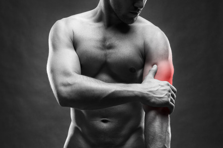 enhanced healthy: Pain in the elbow. Muscular male body. Handsome bodybuilder posing on gray background. Black and white photo with red dot