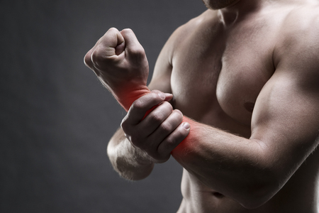 enhanced health: Pain in the hand. Muscular male body. Handsome bodybuilder posing on gray background with red dot