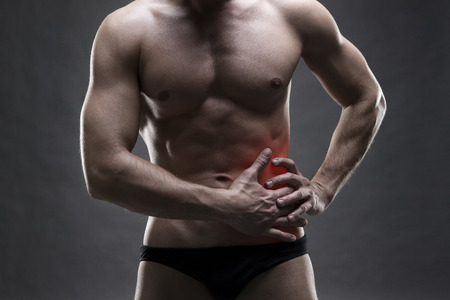 pancreatitis: Pain in the left side. Muscular male body. Handsome bodybuilder posing on gray background with red dot Stock Photo