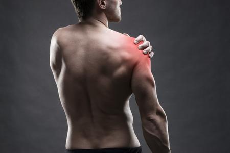 codo: El dolor en el hombro. Carrocería masculina muscular. Guapo fisicoculturista posando sobre fondo gris con el punto rojo