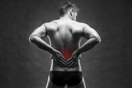 pyelonephritis: Kidney pain. Man with backache. Handsome muscular bodybuilder posing on gray background. Black and white photo with red dot
