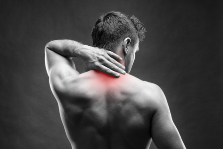 Pain in the neck. Man with backache. Muscular male body. Handsome bodybuilder posing on gray background. Black and white photo with red dot Stock Photo