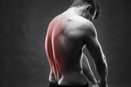 disease cure: Man with backache. Pain in the human body. Muscular male body. Handsome bodybuilder posing on gray background. Black and white photo with red dot Stock Photo
