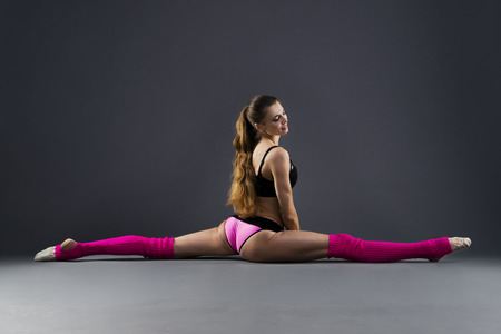 Beautiful muscular woman doing front split with right leg forward. Hanumanasana on a gray background