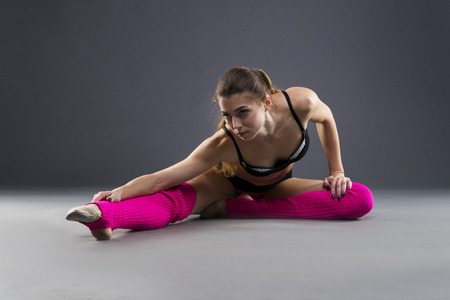 gaiters: Muscular attractive fitness woman warming up in the studio on gray background. Flexible dancer Stock Photo