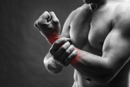 enhanced healthy: Pain in the hand. Muscular male body. Handsome bodybuilder posing on gray background. Black and white photo with red dot