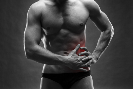 Pain in the left side. Muscular male body. Handsome bodybuilder posing on gray background. Black and white photo with red dot