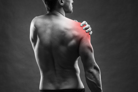 shoulder: Pain in the shoulder. Muscular male body. Handsome bodybuilder posing on gray background. Black and white photo with red dot
