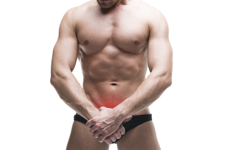underbelly: Man with pain in the prostate. Muscular male body. Handsome bodybuilder posing in studio. Isolated on white background with red dot. Middle part of the body Stock Photo