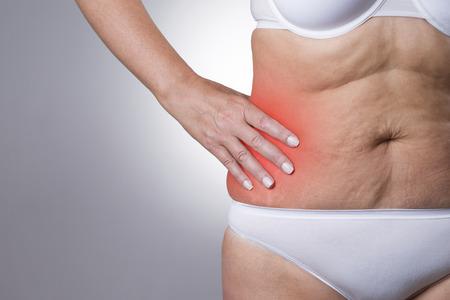 vientre femenino: Mujer con dolor en el lado derecho del cuerpo. El dolor en el cuerpo humano en fondo gris con el punto rojo. tiro del estudio