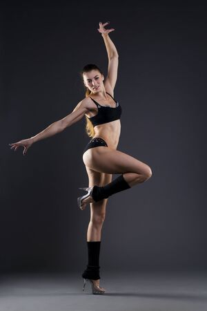 gaiters: Muscular attractive fitness woman on gray background in studio. Trained female body
