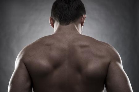 latissimus: Handsome muscular bodybuilder posing on gray background. Low key studio shot. Sexy male body Stock Photo