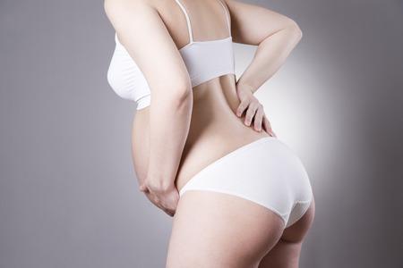 poronienie: Caucasian pregnant woman in white lingerie with abdominal pain on gray studio background. Pregnancy concept Zdjęcie Seryjne
