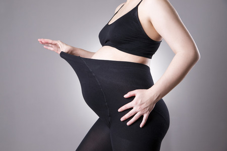 Pregnant woman in black tights for pregnant women on gray background. Front view