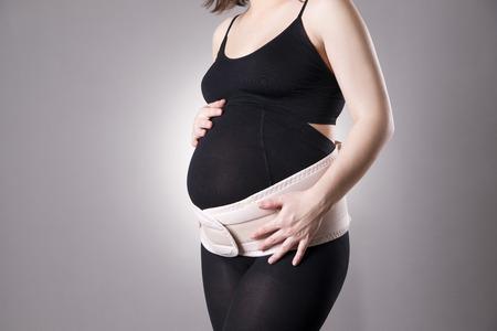 정형 외과 지원 벨트와 함께 젊은 백인 임신 한 여자. 회색 배경에 촬영 스튜디오
