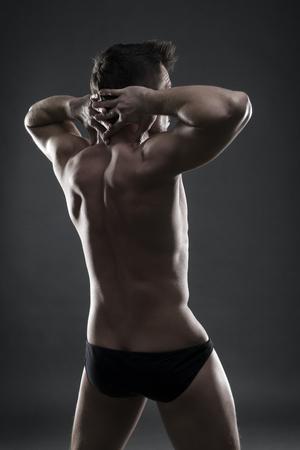 dorsi: Handsome muscular bodybuilder posing on gray background. Low key studio shot. Sexy male body Stock Photo