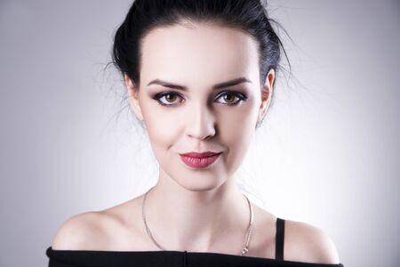 Beautiful woman portrait on a gray background. Professional makeup. Studio shot