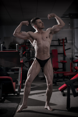 muscled: Handsome bodybuilder posing in gym. Perfect muscular male body. Toning image
