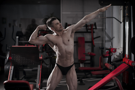 body toning: Handsome bodybuilder posing in gym. Perfect muscular male body. Toning image