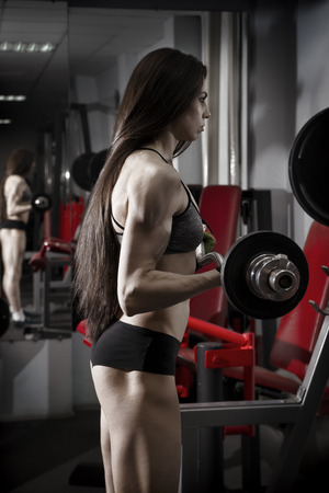 body toning: Young sexy fitness girl workout with barbell in the gym. Brunette fitness woman in sport wear with perfect muscular body. Backlight and toning image