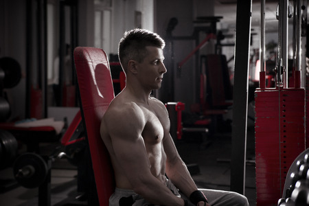 body toning: Handsome bodybuilder works out on athletic bench in gym. Perfect muscular male body. Toning image Stock Photo