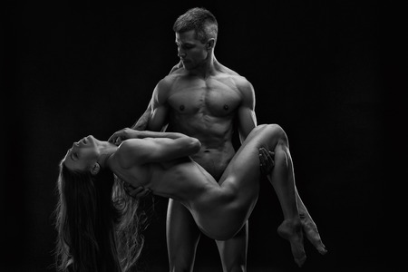 naked black men: Nude sexy couple. Art photo of young adult man and woman. High contrast black and white muscular naked body on black background Stock Photo
