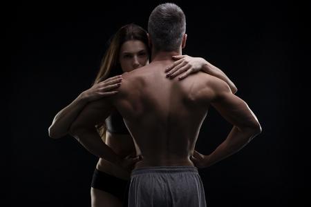 Junge Erwachsene muskulösen Mann und Frau. Sexy Paar auf schwarzem Hintergrund