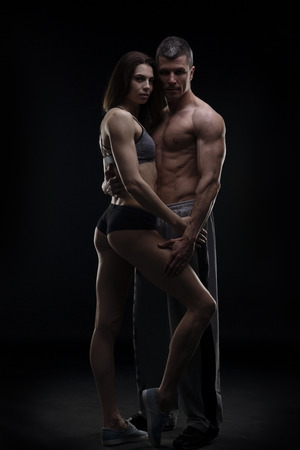sexy couple black background: Young adult muscular man and woman. Sexy couple on black background Stock Photo