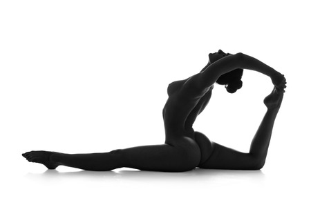 Nude yoga. Artistic photos of beautiful sexy body of young woman with perfect figure. Rajakapotasana pose. Isolated on white background. Studio shot