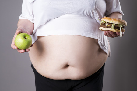 big woman: Women suffer from obesity with big hamburger and apple in hands. Junk food concept on a gray background