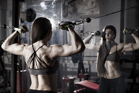 body toning: Young sexy fitness woman workout with training machine in the gym Brunette fitness woman in sport wear with perfect muscular body. Backlight and toning image