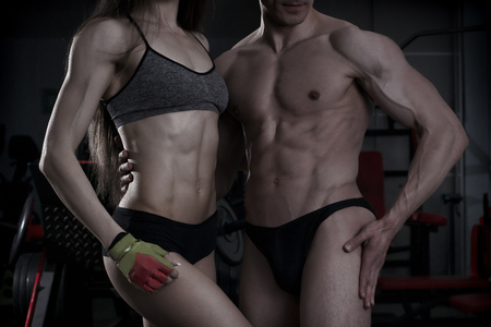 body toning: Young sexy athletic man and woman after fitness exercise. Perfect muscular body. Toning image