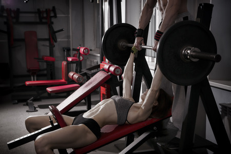 Giovane ragazza di forma fisica di allenamento sexy con bilanciere in palestra. Brunette donna nello sport indossare con corpo muscoloso perfetto. immagine retroilluminazione e tonificazione
