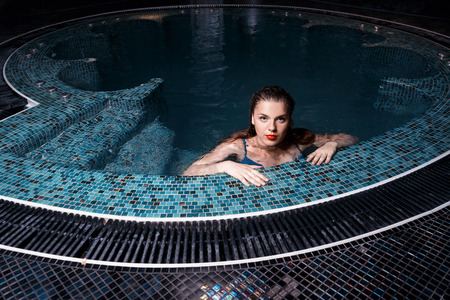 Beautiful young blonde caucasian woman in bikini with waterproof makeup relaxing in hot pool or jacuzzi at spa center, water treatment and body care concept Фото со стока
