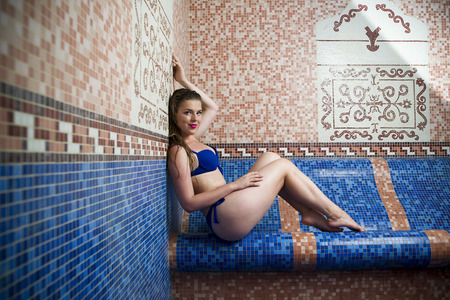 turkish bath: Beautiful young blonde caucasian woman in bikini relaxing in turkish bath at spa center, water treatment and body care concept