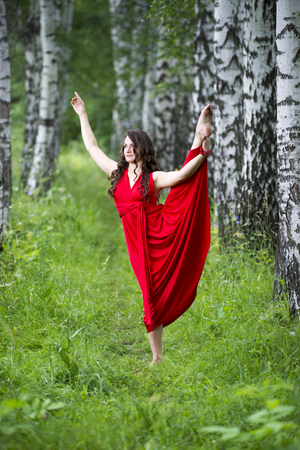 flexibility: Beautiful young caucasian brunette woman in red dress outdoors, whole-length portrait, flexibility and stretching on nature