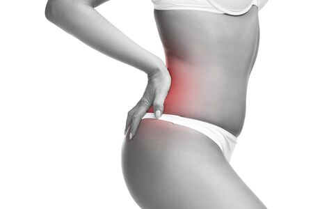 soreness: Woman in underwear with backache, pain in the human body, isolated on white background with red dot Stock Photo