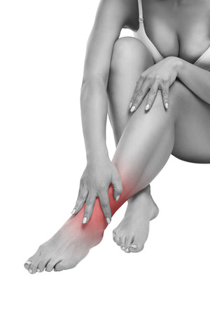 muscle spasm: Woman with pain in the joint, massage of female feet, ache in the human body isolated on white background with red dot Stock Photo