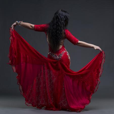 エキゾチックな東の美しい若い女性は、灰色の背景、撮影スタジオにオープン バックと民族の赤いドレスでベリーダンスを実行します。