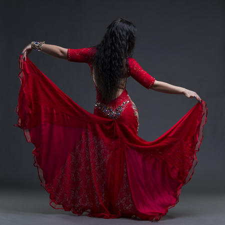 Young beautiful exotic eastern women performs belly dance in ethnic red dress with open back on gray background, studio shot