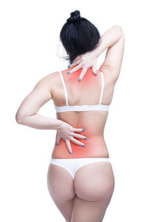 Young caucasian woman in underwear with backache, neck pain in the female body, isolated on white background with red dot, copy space