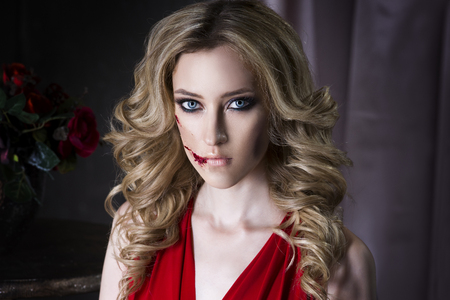 Beautiful young blonde woman in red dress with halloween make up and bloody face art, close up portrait Stock Photo