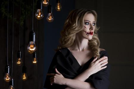mujer golpeada: Hermosa mujer rubia joven vestido de negro con adornos de Halloween maquillaje y arte de la cara con sangre, víctima de la violencia doméstica, cerca retrato Foto de archivo