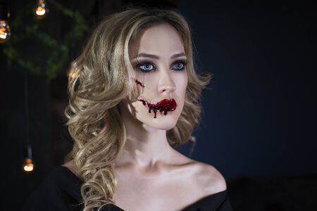 Beautiful young blonde woman in black dress with halloween make up and bloody face art, victim of domestic violence, close up portrait