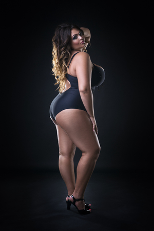 Young beautiful caucasian plus size model in swimsuit, xxl woman on black background, full length portrait Stock Photo
